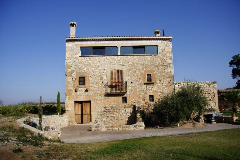 Vista de la façana principal de la casa amb la olivera al costat