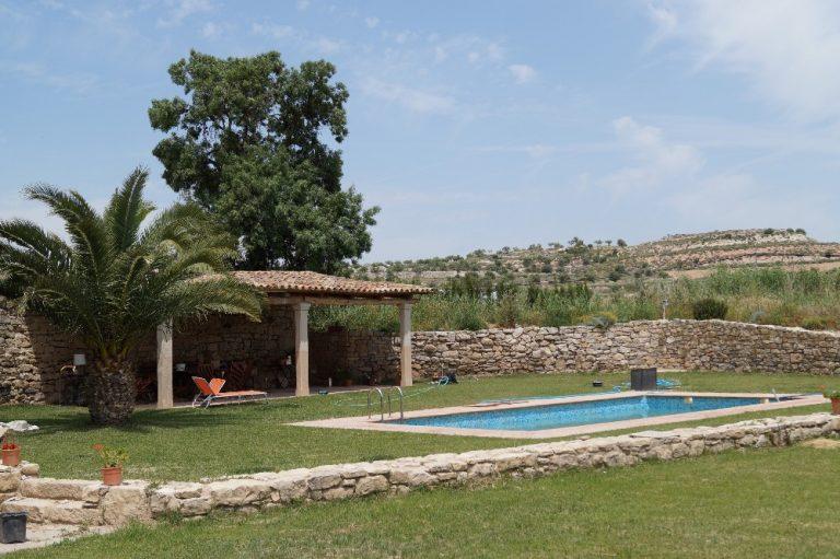 Vista del jardí amb la gespa, la piscina, el porxo i les hamaques per descansar