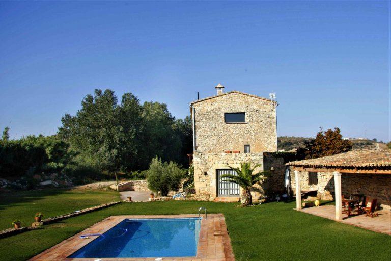 Imatge lateral de la casa amb la piscina , el porxo i el jardí