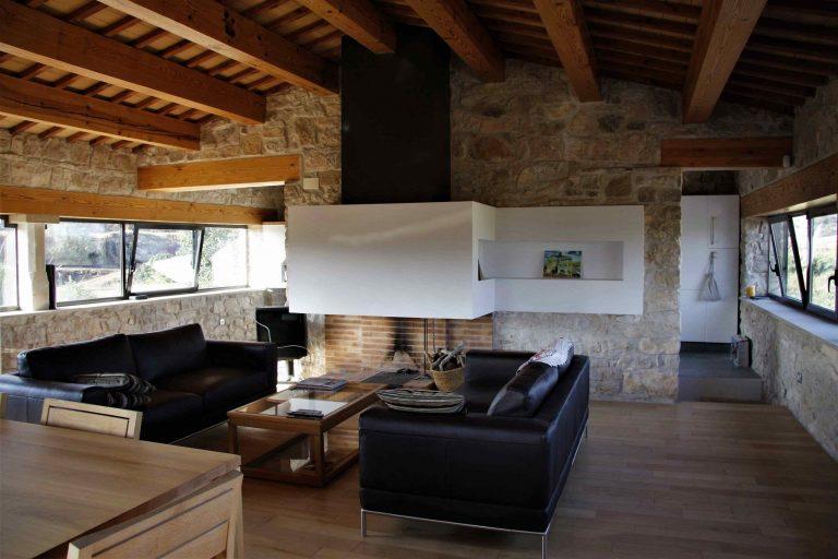 Sala d'estar amb els sofàs y la llar de foc
