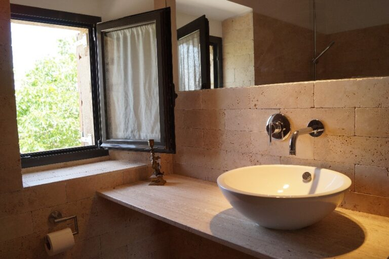 Imatge del bany on es veu la pica y la finestra exterior