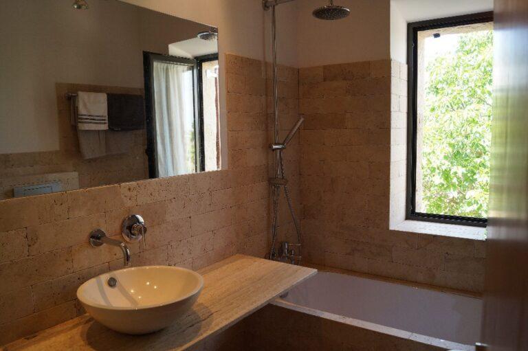 Imatge d'un bany amb la pica, la banyera i la finestra
