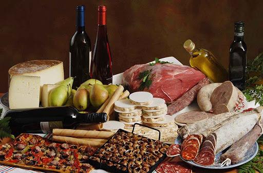 Taula plena de productes tipics de lleida; vi, coca de recapte, oli, turró, caragols, llonganissa,etc