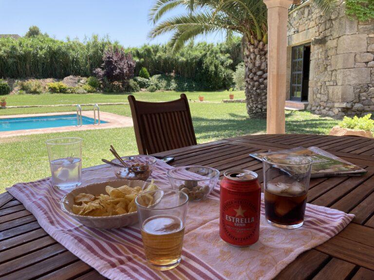 Imagen donde se ve el jardin desde el porche donde en la mesa hay aperitivo